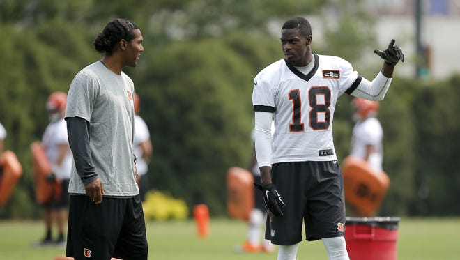 Cincinnati Bengals Bill Walsh Minority Coaching Fellowship program coach T.J. Houshmandzadeh, left, talks with wide receiver A.J. Green during organized team activities, Tuesday, June 9, 2015, on the practice fields adjacent to Paul Brown Stadium. The Enquirer/Kareem Elgazzar