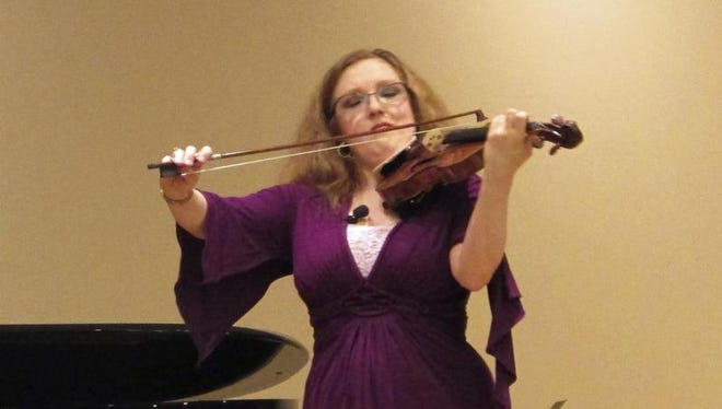 In this April 3, 2016 photo, concert violinist Rachel Barton Pine performs during a master class she was teaching for young violinists at Gail Borden Library in Elgin, Ill. American Airlines apologized to Pine after she was not permitted to board a plane with her antique violin on Wednesday, April 27, 2016. Pine says a flight attendant and captain would not allow her violin as a carry-on from Chicago to Albuquerque.