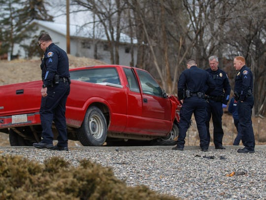 Farmington police officers inspect the vehicle involved in a police pursuit Thursday at 400 Vine Ave. in Farmington.