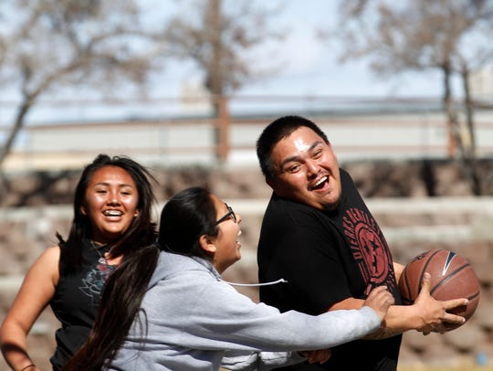 From left, Tenaya Begaii, and Kiona Trujillo play basketball with their father Martin Begaii on Monday at Brookside Park in Farmington.