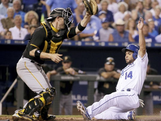 Kansas City Royals' Omar Infante (14) beats the tag at home by Pittsburgh Pirates catcher Chris Stewart to score on a bunt single by Jarrod Dyson during the seventh inning of Wednesday's in Kansas City, Mo.