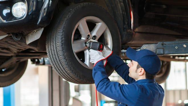 An auto mechanic works on a  wheel.