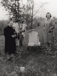 Ladies gather at Mrs. Anderson's gravesite with homestead