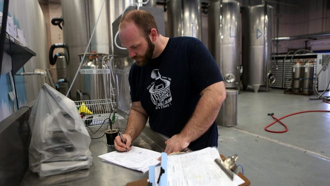 Josh Elliott, lead brewer for Urban Artifact, checks pH levels on a beer at the Northside brewery on Tuesday afternoon.