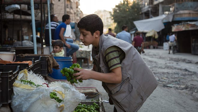 A Syrian boy arranges peppers at a market in the rebel-held area of the northern Syrian city of Aleppo on Sept. 19, 2016, after humanitarian relief failed to enter the city under siege.