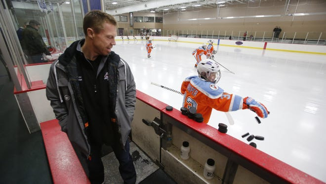 Former Red Wings player and Little Caesars team coach Kris Draper watches his son Kienan Draper in January 2013.