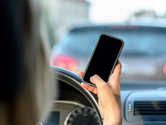 Young woman driver reading a text message