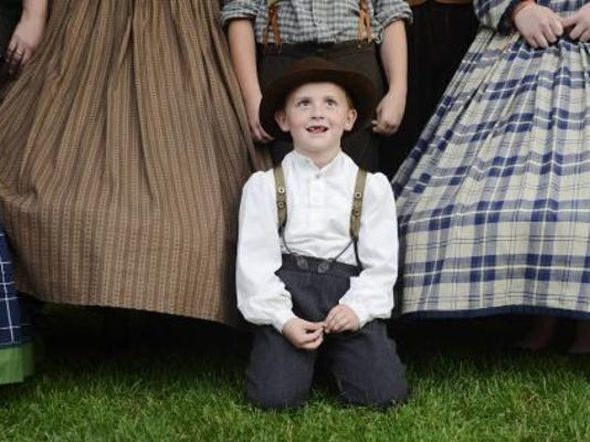 Derick Kinser, 7, of Columbia, poses for a photo with others dressed in period clothes before the commemoration of the 150th anniversary of the burning of the bridge that spans the Susquehanna River from Wrightsville to Columbia. Organizers estimated 12,000 people attended Friday night's event at the John Wright Restaurant in Wrightsville. (DAILY RECORD/SUNDAY NEWS - KATE PENN)