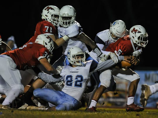 Freehold Township's Artie Bader (#22) tries to rip the ball free from Manalapan's Naim Mayfield in the NJSIAA Central Group IV semifinal football game in Manalapan on Nov. 17, 2017.