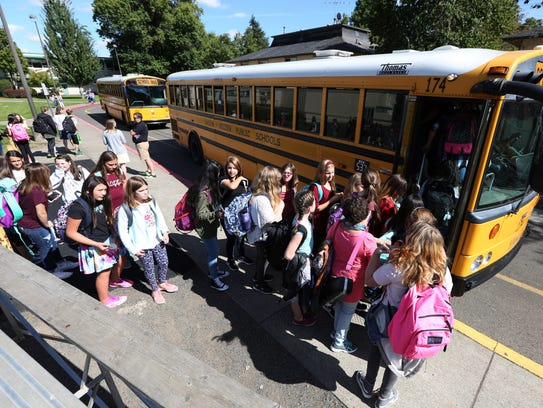 Students board buses at the end of the first day of