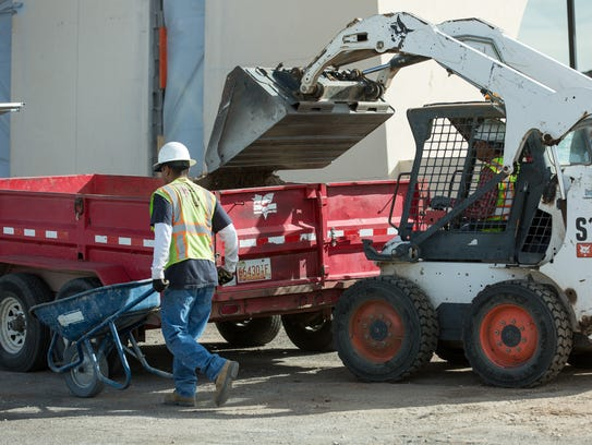 Workers with Landscape and Design move dirt Tuesday,