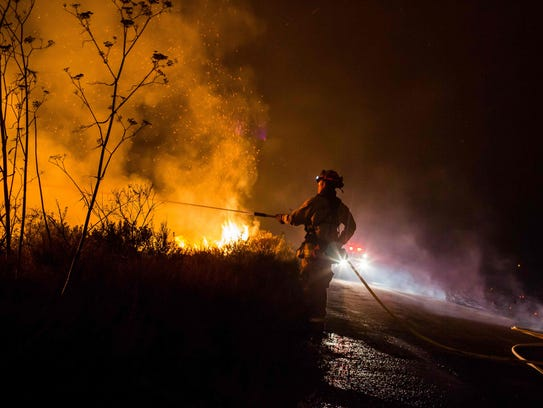 Firefighters work to extinguish the Thomas Fire as