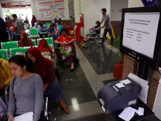 Patients wait near a queue number dispenser affected