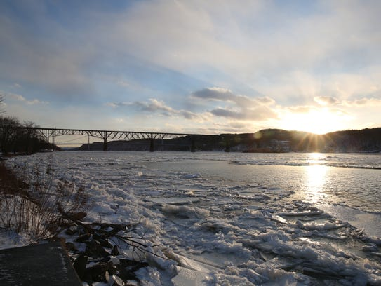 The sun sets behind the Walkway Over the Hudson as sheets of ice wash up on shore Jan. 5.