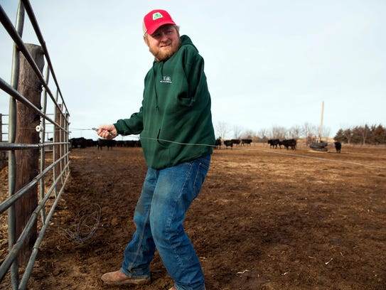 Kyle Lammers repairs an electric fence Friday, Jan
