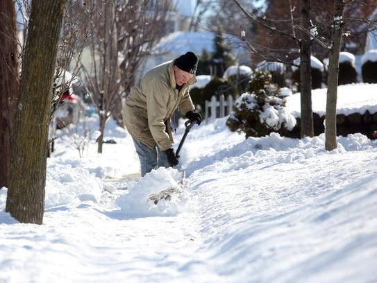Mike McGuire of Tarrytown clears the snow outside his