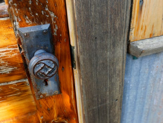 The front door, made of reclaimed wood, is adorned