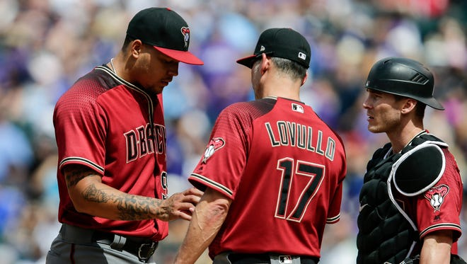 May 7, 2017; Denver, CO, USA; Arizona Diamondbacks starting pitcher Taijuan Walker (99) hands the ball off to manager Torey Lovullo (17) after being pulled in the sixth inning against the Colorado Rockies at Coors Field.