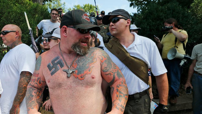 This Aug. 12, 2017 image shows a white supremacist sporting a NAZI tattoo leaves Emancipation Park in Charlottesville, Va.