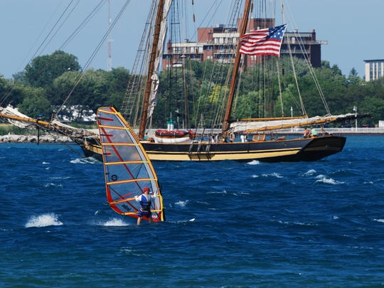 A sailboarder shares the St. Clair River with the USS