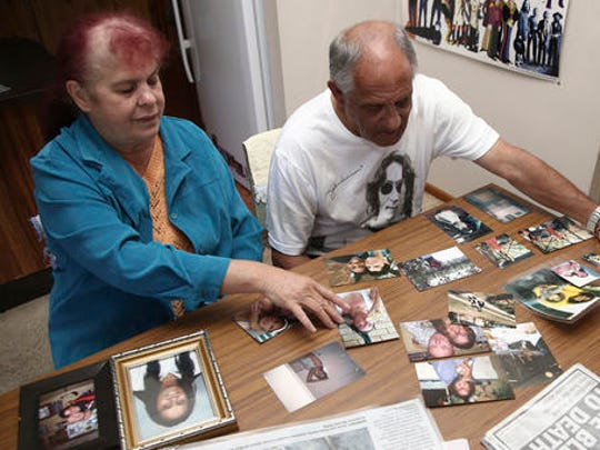 In this Aug. 15, 2016 photo, Gordon Davis and his wife Thelma look through photos of their daughter, Lynette Daley, at their home in Yamba, Australia. The brutal death of Daley, an Aboriginal woman, and the reluctance of officials to prosecute the white suspects, has highlighted a deadly racial divide in Australia, where Indigenous people remain the most disadvantaged segment of society.