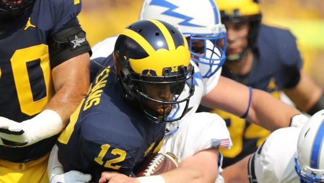 Michigan's Chris Evans is tackled by Air Force defenders in the first quarter Saturday, Sept. 16, 2017 at Michigan Stadium.