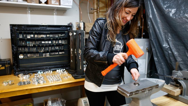 Misty Nagan, owner of SilverWear by Misty, flattens a spoon against an anvil to create a ring in her De Pere studio. She scours antique stores to find vintage silverware to create her jewelry.