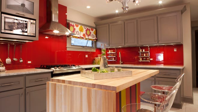 In this photo provided by HGTV, Designer and host of HGTV's Great Rooms, Meg Caswell, painted the walls red then added a clear glass cover to create a chic, vibrant backsplash.  Elements like this, as well as stools, countertop appliances and textiles are great ways to inject color into a kitchen that may have more traditional bones for a look that?s unexpected and modern. (AP Photo/HGTV)