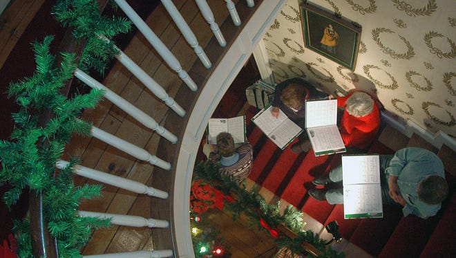 Carolers sit on the steps, entertaining guest at the home of famous author  Louis Bromfield during a past Candlelight Holiday tour at Malabar Farm.