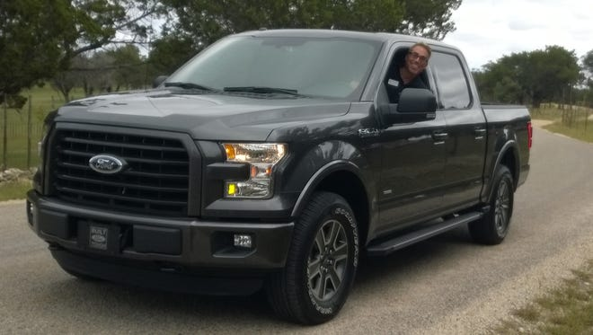 Pete Reyes, chief engineer of the aluminum-body 2015 Ford F-150 pickup, gets a bit of fresh air on the Texas back roads Oct. 1, 2014 during a day of drives by auto writers.