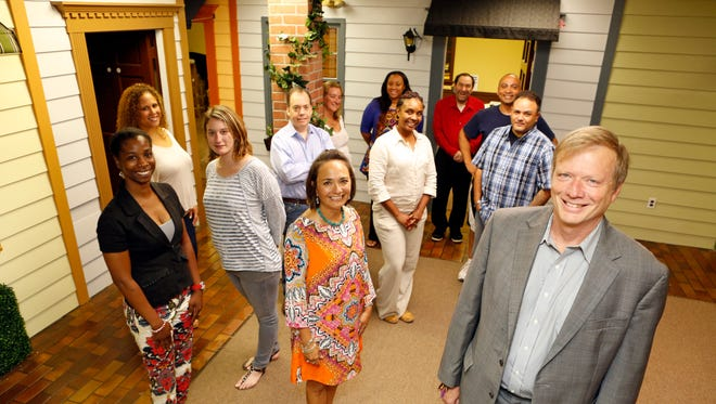 Guy Fessenden, right, the executive director of CHOICE, a mental health agency, with staff members in the organization's new White Plains space, Sept. 10, 2015. The space was designed to look more pleasant by making the exterior of offices look like homes.