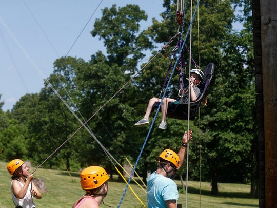 Staff members help Chance Presley ascend the climbing wall at Camp Barnabas on Wednesday, June13, 2018.