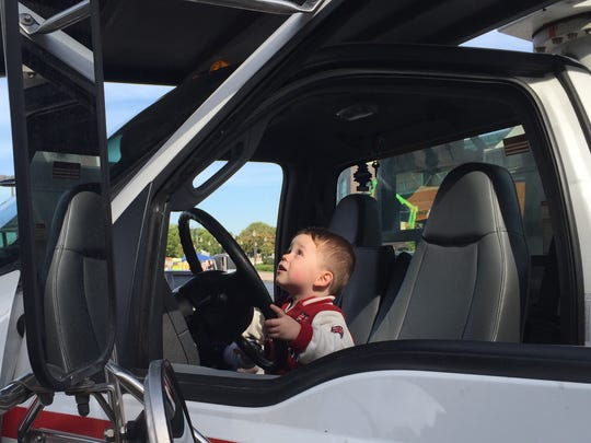 Carter Graham, 2, of Penfield, plays in a bucket truck