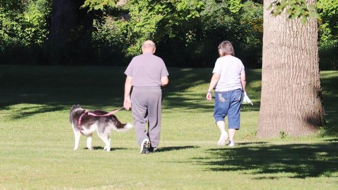 This couple enjoys a walk in Chautauqua Park with their canine companion Thursday morning.