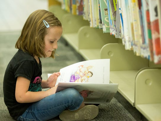 Molly Harper, 6, of Las Cruces, reads in the children's