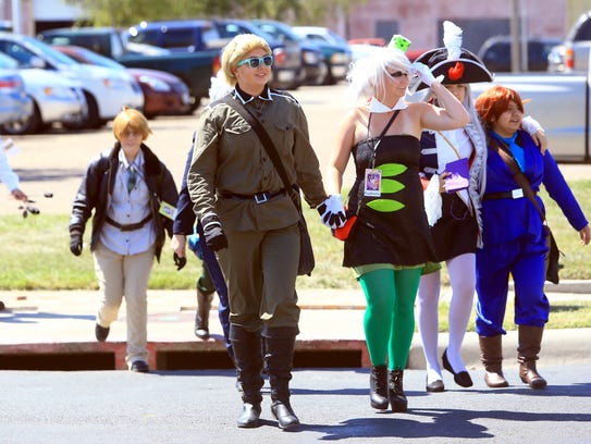 Cosplayers cross the street as to the Realms Con on