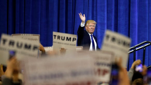 Donald Trump waves as he steps on stage to speak at