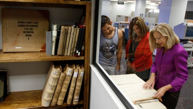 Nicholas Bejelis and Rita GEEHAN-Miller look at Lee County historical records presented by Lee Clerk of the Circuit Court & Comptroller Linda Doggett at the Lee County clerk's office Thursday.