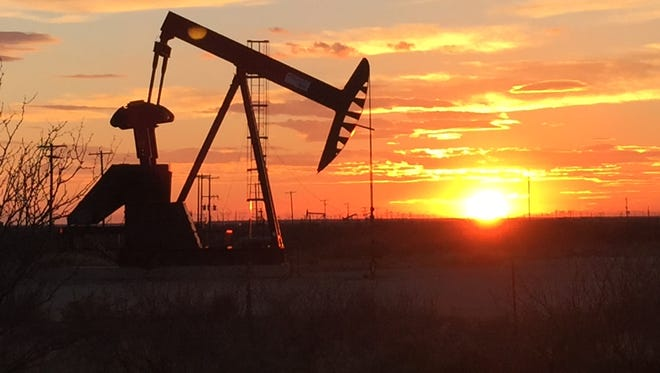 A pump jack sucks oil from the ground outside Odessa as the sun sets.