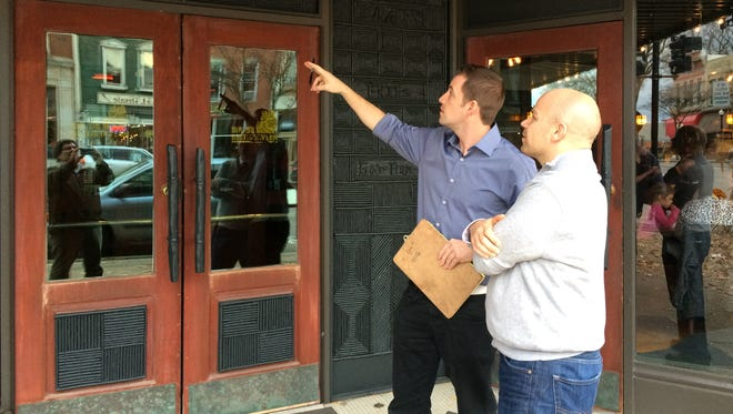 Adam Merkel (pointing) and Ryan McLean inspect the front of Mr. B's Rustic Tavern.