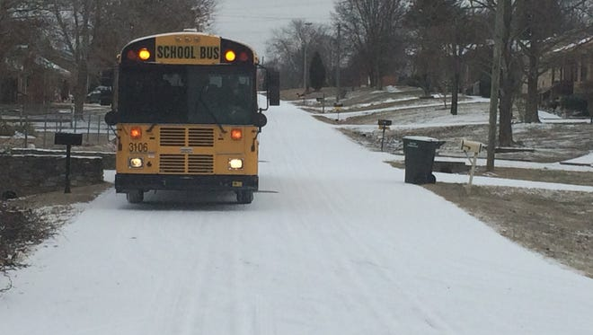 A Robertson County School bus prepares to drop off a student as snow falls.