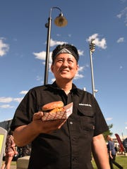 Food trucks from New Jersey and Philadelphia battle it out at this year's Food Truck Mash-Up, hosted by North Jersey Events at the Meadowlands Racetrack in East Rutherford on Saturday June 03, 2017. Robert Austin Cho of Kimchi Smoke holding a Chonut.