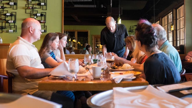 Kevin Weiss, center, serves a family during brunch at Dusty's Cellar in Okemos.