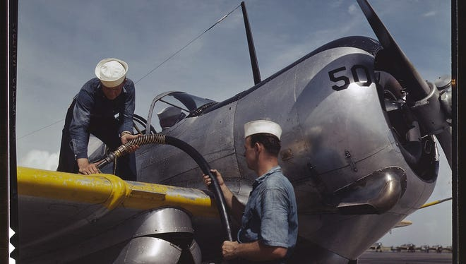 Feeding an SNC advanced training plane its essential supply of gasoline is done by sailor mechanics at the Naval Air Base, Corpus Christi, Texas. Standing on the wing is Floyd Helphrey who came from Iowa to join the Navy early in the year. At right is W. Gardner of Illinois who used to be a crane operator. Image was taken in August 1942 by the Office of War Information and resides in the Library of Congress.