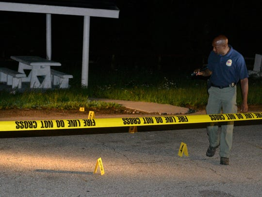 A MBI officer helps process the scene Tuesday morning