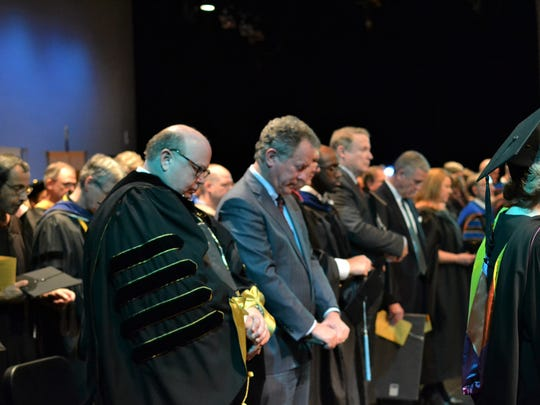 Anderson University President Evans Whitaker rests his head while standing beside Gov. David Beasley, who was the keynote speaker Wednesday at the school's Founders Day Convocation.