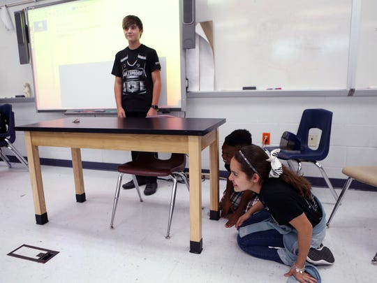 Metro Elementary School of Design and BullyProof program participants Jacob Zirbes (from left), 12, Zeon Baldwin, 12, and Jadyn Urtado, 12, hide as they participate in charades during a meeting at the school on May 16, 2017. The charades were part of a lesson on nonverbal communications.