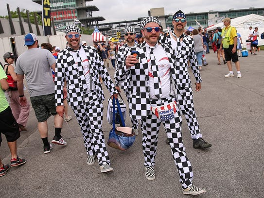 A group of race fans are clad in checkered attire,