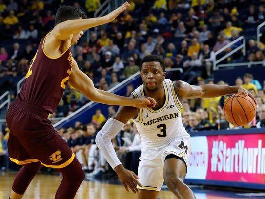 Michigan guard Zavier Simpson (3) dribbles defended