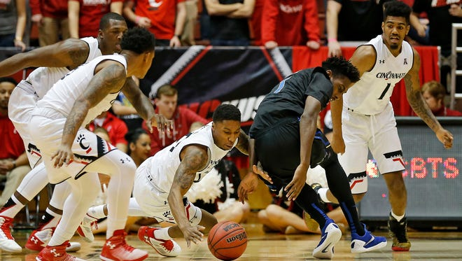 Cincinnati Bearcats guard Kevin Johnson (25) dives for a ball mishandled by Tulsa Golden Hurricane guard Rashad Smith (1) in the first half of the American Athletic Conference NCAA mens basketball game between the Cincinnati Bearcats and the Tulsa Golden Hurricane at Fifth Third Arena on the campus of the University of Cincinnati on Saturday, Jan. 2, 2016.